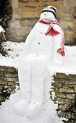 © Licensed to London News Pictures. 20 January 2013. Chipping Norton, Oxfordshire. Snowman watches the sledging.Probably the best Street in England for sledging? Residents of The Leys in Chipping Norton have made a super sledging run in the road. The local children even prevented council workers from salting the road by sitting down across the road to block the gritters. Everyone who live in the Leys seems to love the sledging run and have even joked that they want to apply for a ski lift to be installed for future years fun.. Photo credit : MarkHemsworth/LNP