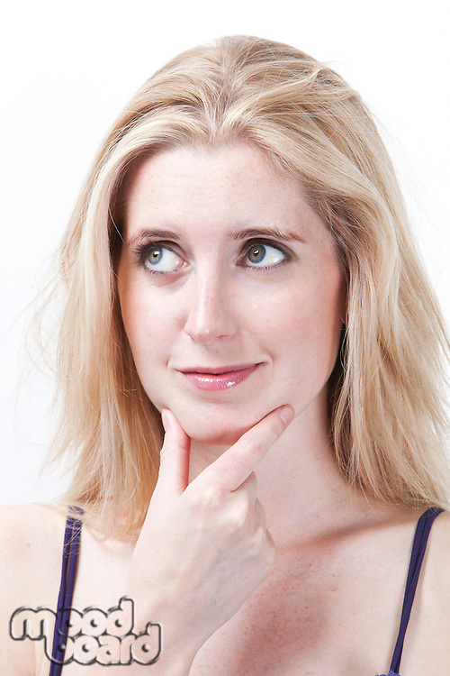 Thoughtful young woman with hand on chin looking away against white background