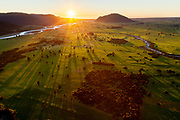 The setting sun casts long shadows over lush farmland dotted with native trees. The Kokatahi River is on the right and the Hokitika River is on the left. Mt Camelback can be seen to the right of the setting sun.