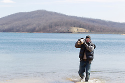 rugged good looking man carrying a large log in a lake during the winter