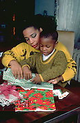 Mother age 38 helping 6 year old son wrap Christmas gifts. St Paul Minnesota USA