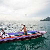 A man throws a fish bomb off a boat, Kota Kinabalu, Borneo, Malaysia, South China Sea,