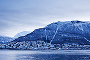 View of Storsteinen and Tromsdalen below, in the winter twilight after overnight snowfall, from the harbour area of Tromsø.