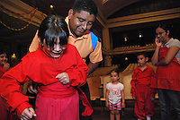"USA, Chicago, July 2nd - 23rd, 2009.  Professional instructor Ruben Pachas, who is Peruvian, helps a dancer put on her costume before a dress rehearsal. For almost 20 years, Polo Garcia, a professional dance teacher from ""America Baila,"" has been giving traditional South American dance lessons at various Pilsen and Little Village schools, including Maria Saucedo Scholastic Academy, whose turn-of-the-century auditorium is featured here. Garcia, who is Mexican, does the research for these dances in-person, makes the costumes himself, and provides free summer classes. He works with Claudio Rabadan, a former Saucedo student.  Photographs for HOY by Jay Dunn."
