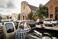 The Rev. Gregory T. Manning, pastor of Gloria Dei Lutheran Church, assists Altia Reed with bagged food from the Broadmoor Food Pantry next to the church (pictured in rear) on Wednesday, March 9, 2016, in New Orleans. LCMS Communications/Erik M. Lunsford