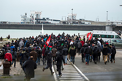 © Licensed to London News Pictures. 23/01/2016. Calais, France. A group of migrants storm towards the port of Calais in Northern France during a demonstration through the town centre of Calais, on the same day that Leader of the Labour Party JEREMY CORBYN visited the migrant camp known as the 'Jungle' . Photo credit: Ben Cawthra/LNP