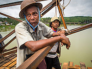 16 SEPTEMBER 2014 - SANGKHLA BURI, KANCHANABURI, THAILAND: Members of the Mon community watch Thai soldiers work on the repair of the Mon Bridge. The 2800 foot long (850 meters) Saphan Mon (Mon Bridge) spans the Song Kalia River. It is reportedly second longest wooden bridge in the world. The bridge was severely damaged during heavy rainfall in July 2013 when its 230 foot middle section  (70 meters) collapsed during flooding. Officially known as Uttamanusorn Bridge, the bridge has been used by people in Sangkhla Buri (also known as Sangkhlaburi) for 20 years. The bridge was was conceived by Luang Pho Uttama, the late abbot of of Wat Wang Wiwekaram, and was built by hand by Mon refugees from Myanmar (then Burma). The wooden bridge is one of the leading tourist attractions in Kanchanaburi province. The loss of the bridge has hurt the economy of the Mon community opposite Sangkhla Buri. The repair has taken far longer than expected. Thai Prime Minister General Prayuth Chan-ocha ordered an engineer unit of the Royal Thai Army to help the local Mon population repair the bridge. Local people said they hope the bridge is repaired by the end November, which is when the tourist season starts.    PHOTO BY JACK KURTZ