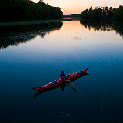 A woman kayaks on the upper reaches of the York River in York, Maine.  High tide.  Sunset.