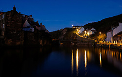 © Licensed to London News Pictures.02/10/15<br /> Staithes, UK. <br /> <br /> Street lights shine on houses and reflect in the water of the harbour as dawn breaks in the North Yorkshire village of Staithes on the east coast as the warm autumn weather continues.<br /> <br /> Photo credit : Ian Forsyth/LNP