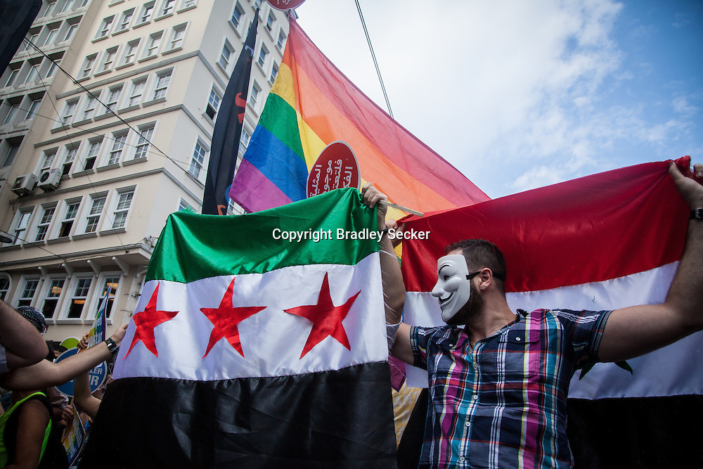 Syrian participants at Istanbul Pride hold both government and opposition flags, with the rainbow flag symbolising the LGBT community's pride and fight for equality in society. Istanbul, Turkey, June 30th 2013