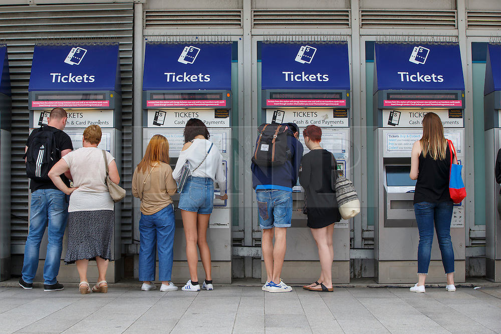 © Licensed to London News Pictures. 16/08/2016. London, UK. Train passengers buy tickets from ticket machines outside London Bridge station in London on Tuesday, 16 August 2016. Rail fares will increase by 1.9% in January 2017, amid renewed calls from campaigners for the nationalisation of rail companies. Photo credit: Tolga Akmen/LNP
