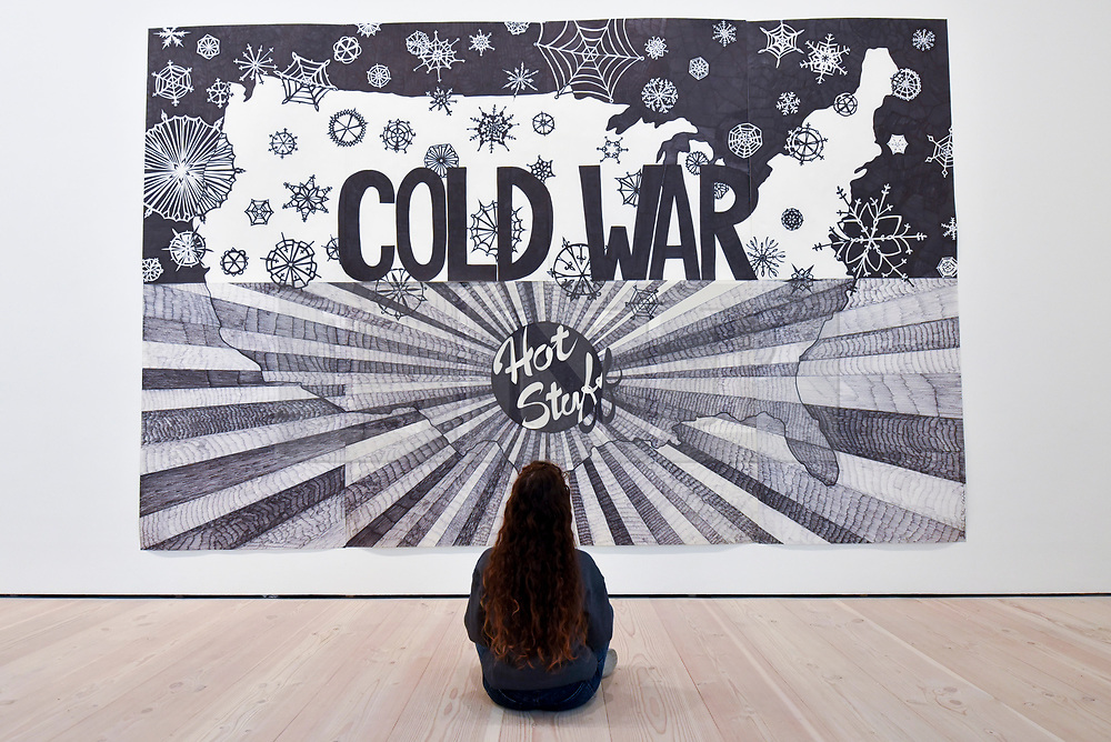 "© Licensed to London News Pictures. 27/09/2018. LONDON, UK. A staff member views ""Cold War"", 2005, by Aleksandra Mir.  Preview of ""Black Mirror"", a major new exhibition featuring the work of 26 contemporary artists, at the Saatchi Gallery.  The show explores art's role in social satire and how political uncertainty has influenced art of recent years and runs 28 September to 13 January 2019.   Photo credit: Stephen Chung/LNP"