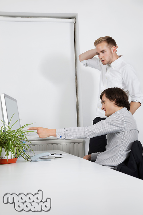 Young businessman showing computer screen to confused coworker at desk