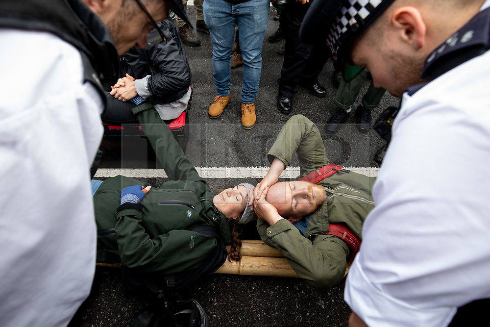 © Licensed to London News Pictures. 07/10/2019. London, UK. Climate change activists are moved on by police following a sit down demonstration on Westminster Bridge, London, closing the entire bridge to traffic, as part of a wider two week long demonstration to cause disruption in the capital. The activists are calling for the government to acknowledge and act on climate change. Photo credit : Tom Nicholson/LNP