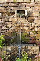 water spout from dry stone wall