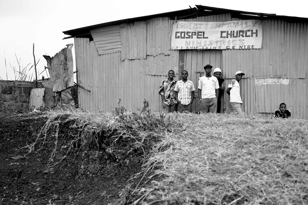 Community residents stand under the awning of a gospel church in Nairobi, Kenya as a summer storm passes by.
