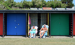 Image ©Licensed to i-Images Picture Agency. 21/06/2014.<br /> <br /> A couple soak up the hot sun outside their beach hut on the sea front in Southsea, Portsmouth.<br /> <br /> Th first day of summer weather pictures in Portsmouth, Hampshire, UK.<br /> <br /> Saturday 21st of June 2014.<br /> Picture by Ben Stevens / i-Images