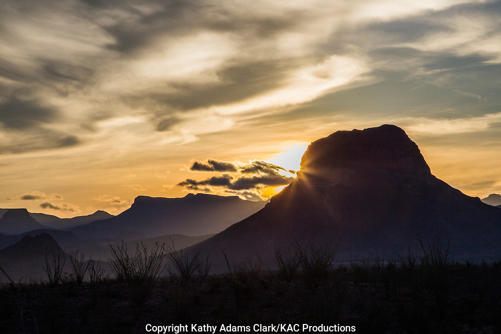 Sun rays or sunburst at edge of silhouetted mouintain at sunrise at Big Bend National Park, Texas.