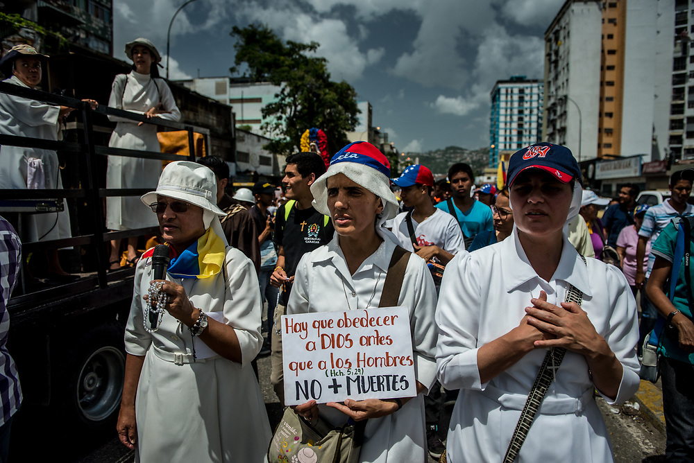 "CARACAS, VENEZUELA - MAY 27, 2017: A nun marches in protest, holding a sign with the Acts 5:29 Bible scripture that says, in Spanish, ""We must obey God rather than men"" and ""No More Deaths"". Priests, nuns and hundreds of other Catholics participate in a peaceful protest against government violence in Caracas. The streets of Caracas and other cities across Venezuela have been filled with tens of thousands of demonstrators for nearly 100 days of massive protests, held since April 1st. Protesters are enraged at the government for becoming an increasingly repressive, authoritarian regime that has delayed elections, used armed government loyalist to threaten dissidents, called for the Constitution to be re-written to favor them, jailed and tortured protesters and members of the political opposition, and whose corruption and failed economic policy has caused the current economic crisis that has led to widespread food and medicine shortages across the country.  Independent local media report nearly 100 people have been killed during protests and protest-related riots and looting.  The government currently only officially reports 75 deaths.  Over 2,000 people have been injured, and over 3,000 protesters have been detained by authorities.  PHOTO: Meridith Kohut"