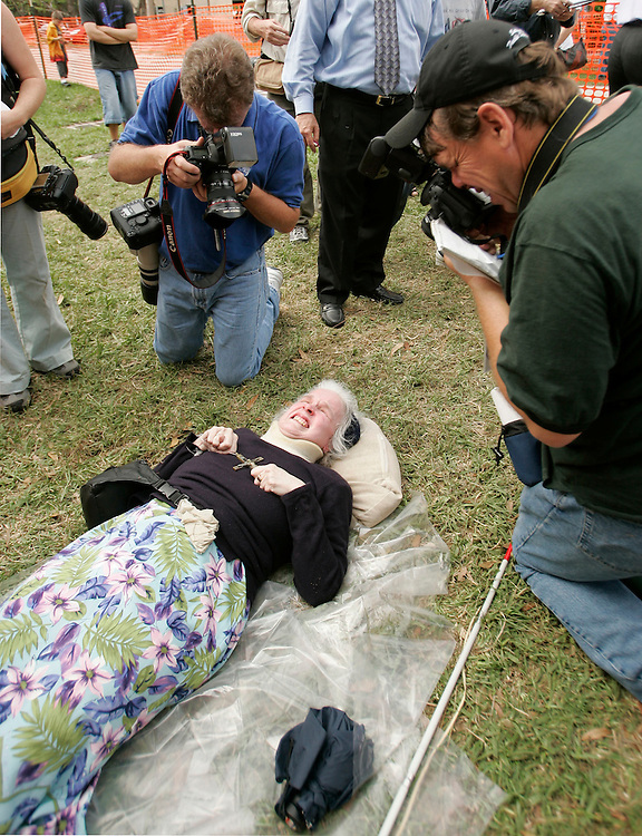 Media photographers surround Patricia Devlin, of Lubbock, Texas as she weeps while praying for the brain damaged Terri Schaivo in front of the Woodside Hospice on March 24, 2005 in Pinellas Park, Florida. REUTERS/Scott Audette