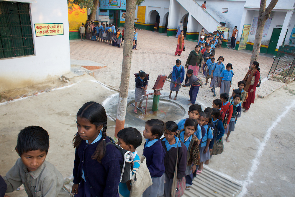 Pupils at Kachnar primary school pass the school handpump as they leave for home. Kachnar primary school in Varanasi district boasts newly renovated toilets for boys and girls. There is a handwashing area and painted slogans on building walls encourage good hygiene practice. The school has a hand pump that supplies drinking water...UNICEF and the Uttar Pradesh Government, have identified 100 model Gram Panchayats (local-level village administration) in Varanasi District (out of a total of 702). The promotion of good sanitation and hygiene practices in these Gram Panchayats allows them to serve as examples for the remaining areas of the district to emulate. The promotion of hygiene and sanitation includes the construction and painting of school toilet blocks, the construction of individual toilets in households, the digging of garbage pits, recycling waste water and encouraging personal hygiene awareness. ..Only 32 percent of those living in Uttar Pradesh, India's largest state, have access to a toilet. Uttar Pradesh faces many challenges in it's efforts to address this deficiency. UNICEF supports the Uttar Pradesh government's sanitation and hygiene project at both the state and district levels. UNICEF is working to increase the capacity of all of those involved in the sanitation and hygiene project from state-level administrators through to Panchayati Raj (local-level administration) officers and influential individuals, including teachers, who live among rural communities. UNICEF has prioritised the need to communicate the importance of good sanitation and hygiene practice to these communities. The Uttar Pradesh government and UNICEF have focussed their campaign on eight districts (including Varanasi) with the intention that these serve as models for the remaining 62 districts of the state. UNICEF have identified areas of shortcoming within the government program and proposed solutions. These solutions include the proper training of masons, the provision of rural