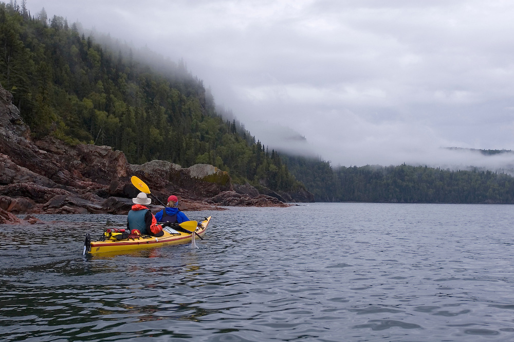 Sea kayakers paddle a tandem kayak on a foggy morning in Lake Superior Provincial Park near Wawa Ontario Canada.