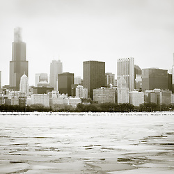 Chicago winter skyline in black and white with frozen ice on Lake Michigan and snow on the lakefront. Photo is high resolution.