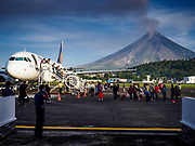 01 FEBRUARY 2018 - LEGAZPI, ALBAY, PHILIPPINES: Passengers get off Philippine Express Airlines flight 2921, from Manila, an Airbus A320, at the Legazpi airport with Mayon volcano in the background. The Mayon volcano started erupting in the middle of January. The airspace around the volcano has been closed off and on for more than week. The airport is about 13 kilometers from the volcano and the ash clouds from Mayon pose a threat to aircraft engines. More than 80,000 people have been evacuated from their homes around the volcano.     PHOTO BY JACK KURTZ