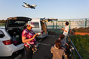 Military Aircraft Enthusiasts at Kamisoyagi Park watch a Japanese Self Defence Force Kawasaki P1 maritime patrol aircraft as it lands at Naval Air Facility, Atsugi airbase, Yamato, Kanagawa, Japan. Thursday April 25th 2019