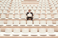 Businessman Using Laptop in Auditorium front view.