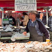 """A fishmonger walks inside his stand under a sign """"Local Squids"""". The Biennale del Gusto is an exhibition held over four days, dedicated to traditional food and drinks from all regions of Italy."""