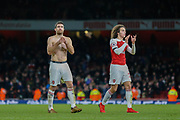 Arsenal defender Sokratis Papastathopoulos (5) and Arsenal midfielder Matteo Guendouzi (29) applaud the fans after the Premier League match between Arsenal and Fulham at the Emirates Stadium, London, England on 1 January 2019.
