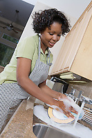Mid-adult woman washing dishes, smiling