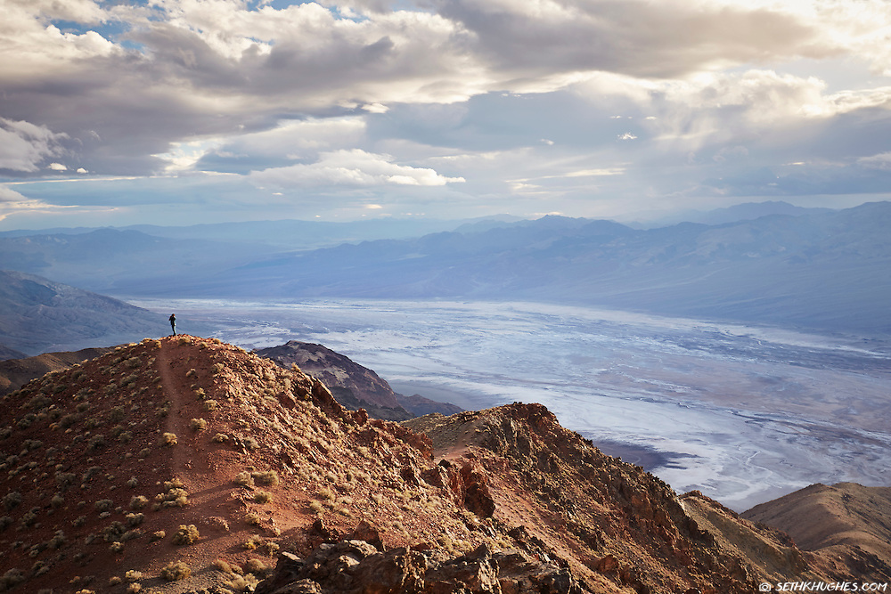 A person in the distance takes a photo of the landscape during sunset at Dantes View in Death Valley National Park.