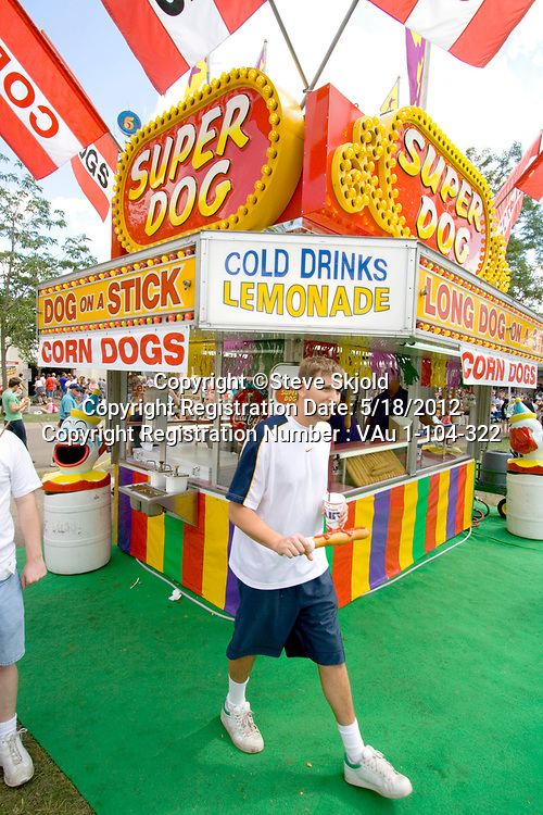 Teenager at a super dog fast food stand with a dog on a stick and lemonade. Minnesota State Fair St Paul Minnesota MN USA