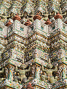 """17 MAY 2013 - BANGKOK, THAILAND:  Hanuman figures support the central prang at Wat Arun. Wat Arun is a Buddhist temple (wat) in the Bangkok Yai district of Bangkok, Thailand, on the west bank of the Chao Phraya River. The full name of the temple is Wat Arunratchawararam Ratchaworamahavihara. The outstanding feature of Wat Arun is its central prang (Khmer-style tower). It may be named """"Temple of the Dawn"""" because the first light of morning reflects off the surface of the temple with a pearly iridescence. Steep steps lead to the two terraces. The height is reported by different sources as between 66,80 m and 86 m. The corners are surrounded by 4 smaller satellite prangs. The prangs are decorated by seashells and bits of porcelain which had previously been used as ballast by boats coming to Bangkok from China. The central prang is topped with a seven-pronged trident, referred to by many sources as the """"trident of Shiva"""". Around the base of the prangs are various figures of ancient Chinese soldiers and animals. Over the second terrace are four statues of the Hindu god Indra riding on Erawan. The temple was built in the days of Thailand's ancient capital of Ayutthaya and originally known as Wat Makok (The Olive Temple). In the ensuing era when Thonburi was capital, King Taksin changed the name to Wat Chaeng. The later King Rama II. changed the name to Wat Arunratchatharam. He restored the temple and enlarged the central prang. The work was finished by King Rama III. King Rama IV gave the temple the present name Wat Arunratchawararam. As a sign of changing times, Wat Arun officially ordained its first westerner, an American, in 2005. The central prang symbolizes Mount Meru of the Indian cosmology. The satellite prangs are devoted to the wind god Phra Phai.     PHOTO BY JACK KURTZ"""