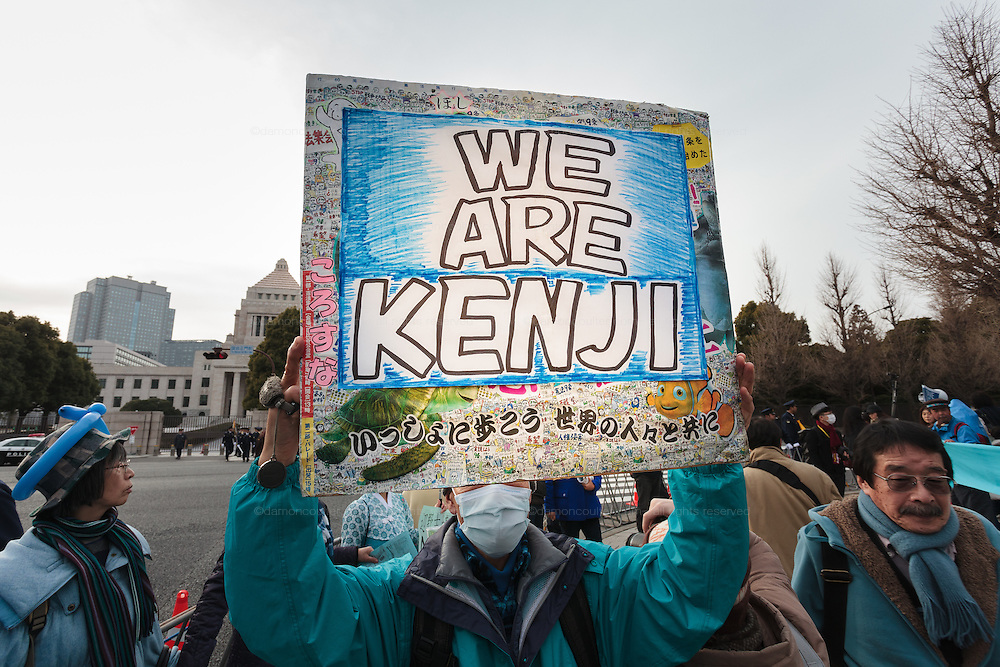 """A man holds a sign reading """"We are Kenji"""" in support of hostage, kenji Goto at a rally to protest the construction of a new US military base at Henoko in Okinawa outside the Japanese National Diet building, Nagatacho, Tokyo, Japan Sunday January 25th 2015. Organisers say 7,000 people joined the protest. Organisers say 7,000 people joined the protest forming a human chain around the Assembly Building."""
