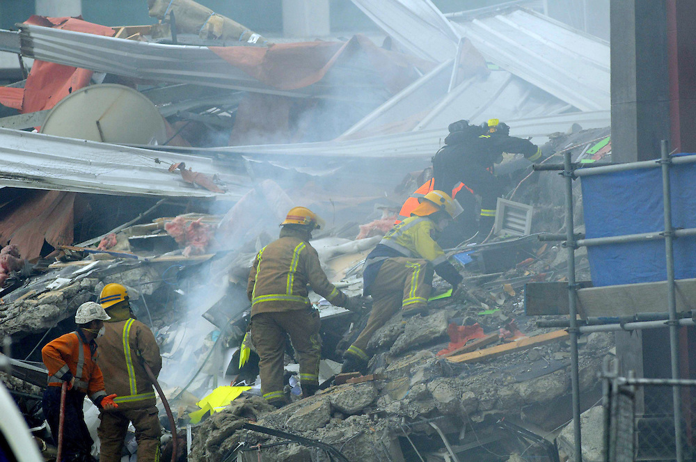 As a helicopter flies overhead with a monsoon bucket trying to supress the fire in a collapsed multilevel office block in Madras Street, rescuers scramble up the rubble  to retrieve a survivor after the 6.3 earthquake, Chritschurch, New Zealand, Tuesday, February 22, 2011. Credit:SNPA / David Wethey