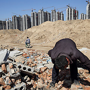 Li Rui, 60, scavenges for building materials in his former village -- now bulldozed into a giant construction site in northeastern China.<br /> <br /> Li was a farmer until three years ago, when the local government announced it would raze down his village and turn farmland into an urban development zone. <br /> <br /> Li said he and other villagers were involuntarily moved to another village. This year Li expects to be resettled into one of the high-rises behind the row of commercial residential buildings in the back of this picture, where former villagers are being relocated en masse.