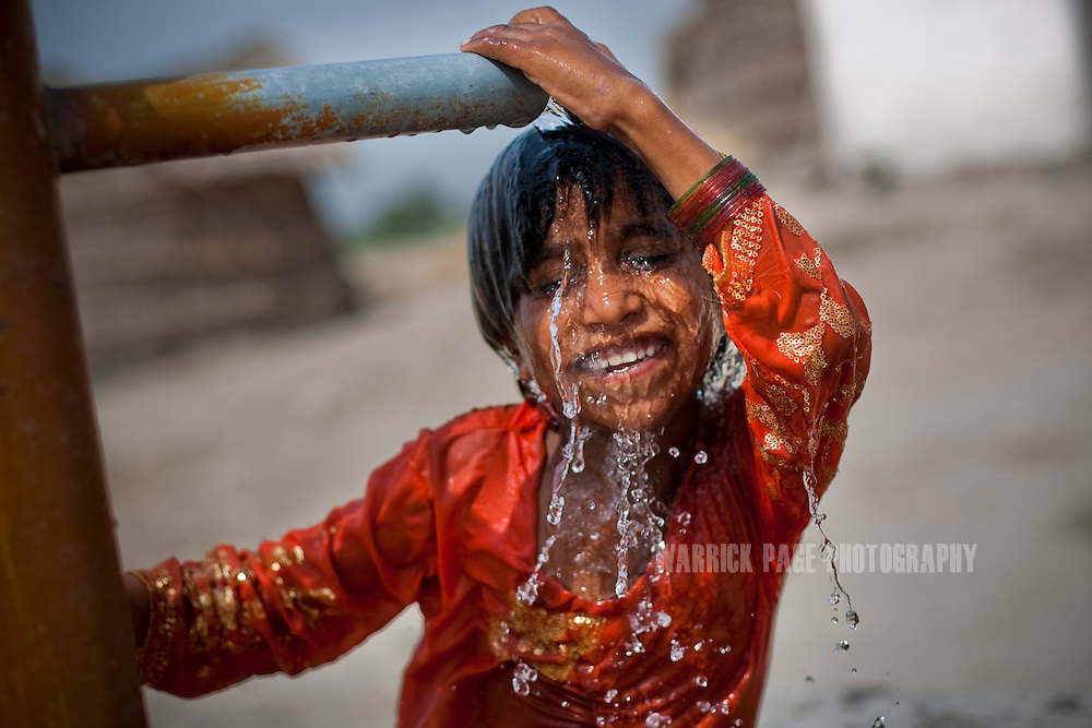 BASTI TIBI, PAKISTAN - JULY 14: A young girl cools herself off under a water pump, on July 14, 2011, in Basti Tibi, Pakistan. Extreme poverty, poor diet and health, exposure to disease, and inadequate sanitation and hygiene annually produce alarming levels of malnutrition amongst children, but the floods of 2010 and 2011 have increasingly endangered an already vulnerable population. Child malnutrition has breached emergency levels in Pakistan - particularly Sindh province - after monsoon floods devastated the country's poorest region for a second year. Malnourishment It is the single biggest contributor to under-five mortality, increasing the risk of infections and slowing recovery from illness. It stuns both mental and physical growth and their future capacity, sapping the next generation's ability to meet the demands of a country already facing an unstable future. According to UN reports, hundreds of thousands of children in Pakistan suffer from severe-acute-malnutrition, with 15.1% of children experiencing acute malnourishment. The Economist recently reported that 44% of children in Pakistan suffer from varying degrees of malnutrition. (Photo by Warrick Page)