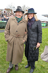 BARRY HUMPHRIES and LIZZIE SPENDER at the 2015 Hennessy Gold Cup held at Newbury Racecourse, Berkshire on 28th November 2015.