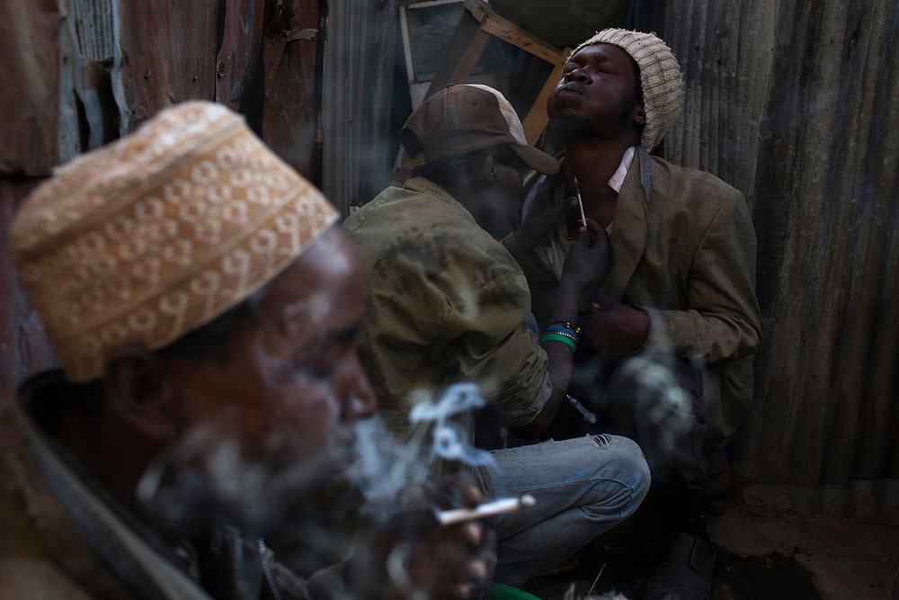 A man smokes a cigarette laced with heroin as Stanley, 36 (C), and Saaid, 32 (R), help each other to inject the drug in Huruma in Nairobi.