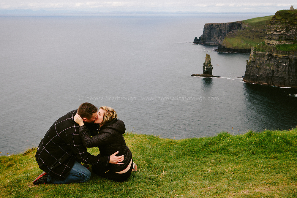 A newly engaged couple kisses at the Cliffs of Moher, Clare, Ireland