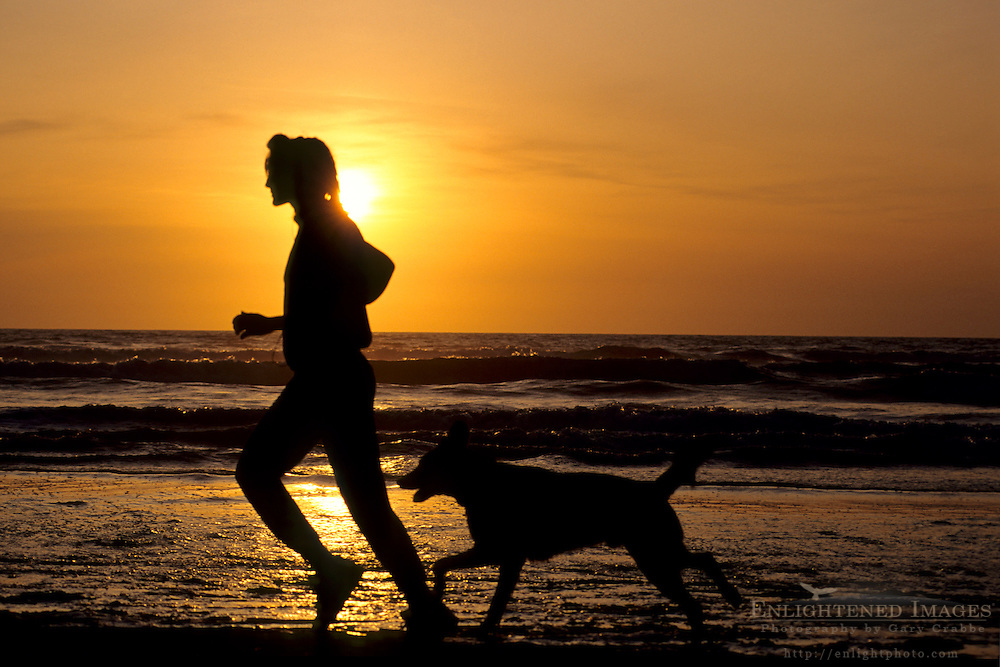 Woman and pet dog running on beach at sunset, near Samoa, Humboldt County, California