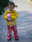 Chinese Child plays with soap bubbles