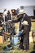 Amish father and son inspect farm equipment during the Annual Mud Sale to support the Fire Department  in Gordonville, PA.