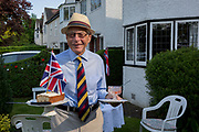 As the Coronavirus lockdown continues over the May Bank Holiday, the nation commemorates the 75th anniversary of VE Day (Victory in Europe Day, the day that Germany officially surrendered in 1945) and in Dulwich, neighbours and residents emerge from their homes to party while still observing social distancing rules. Local Dulwich shop owner and historian, Brian Green takes home-made cake back into his house after taking tea with distanced friends in his front garden, on 8th May 2020, in London, England.