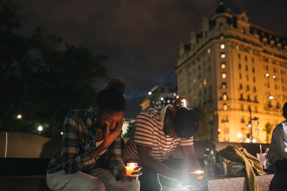 WASHINGTON, DC - SEPTEMBER 16:  Brittany Carter, of Bowie, MD., left, and Jibri Johnson, of Landon, MD. right, hold candles in remembrance of people affected by gun violence during a vigil at Freedom Plaza in Washington, D.C. on Sept. 16, 2013. The vigil, during which organizers called for stricter gun laws, was in remembrance of the more than 10 killed in a shooting at the Navy Yard earlier in the day.   (Photo by Greg Kahn/Getty Images)