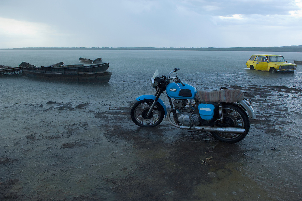 Fishermans motorcycle in water near a car and boats, in rain, Lake Belau, Moldova, June 2009