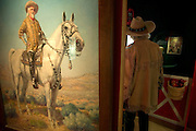 A Buffalo Bill impersanator walks past a Buffalo Bill painting